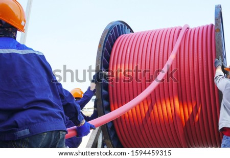 Workers pulling high voltage cable line or large electric cable from big steel cable drum in chemical plants, power plants, oil & gas industry or onshore.