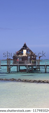 workers repairing an over water bungalow