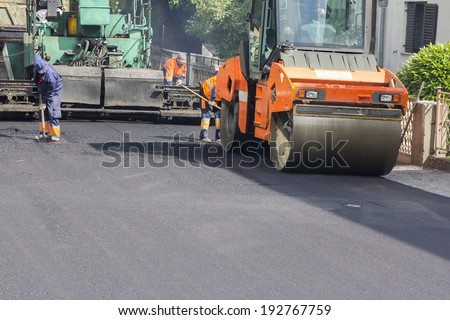 Workers, roller and operating asphalt paver machine during road construction and repairing works
