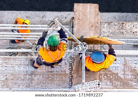 Workers seen from above setting scaffolding on a facade Сток-фото ©
