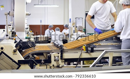 workers sort biscuits on a conveyor belt in a factory - production in the food industry
