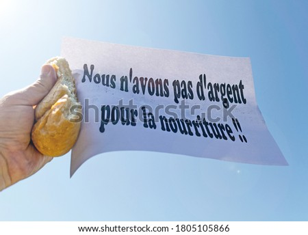 Workers' strike. A worker holds in his hand a piece of bread and a banner, with the message ' Nous n'avons pas d'argent pour la nourriture'- We have no money for food- in french Foto stock ©