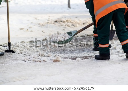 Workers sweep snow from road in winter. Cleaning road from snow storm