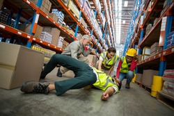 Workers taking care about their colleague lying on the floor in a warehouse