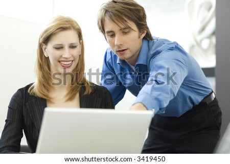 Workers talk while using a laptop computer