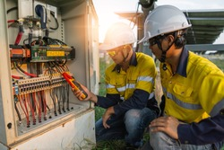 Workers use clamp meter to measure the current of electrical wires produced from solar energy for confirm to normal current.