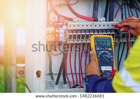 Workers use Multimeter to measure the voltage of electrical wires produced from solar energy for confirm to systems working normal. #1482236681