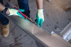 Workers use scissors to cut the metal sheet .