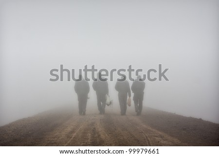 workers walking trail through the fog