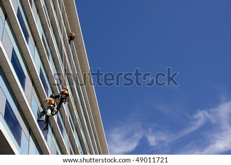 Workers washing the windows facade of a modern office building (cleaning glass service)