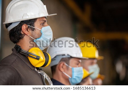Photo of  Workers wear protective face masks for safety in machine industrial factory.