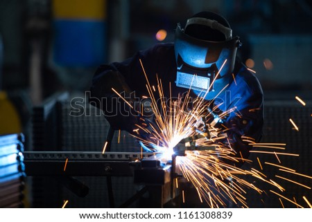 Workers wearing industrial uniforms and Welded Iron Mask at Steel welding plants, industrial safety first concept. Photo stock ©