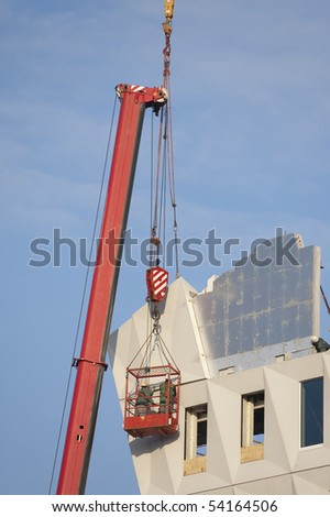 Workers wearing safety harnesses are assisting the placing of a prefab concrete element