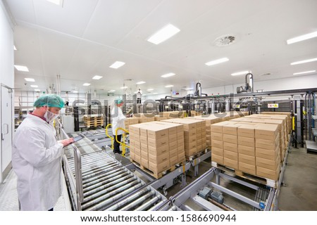 Workers with digital tablets at food packaging production line