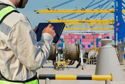 Workers with tablet in hand holding in port and Mooring winches on deck for container ship, forward mooring winch rope background