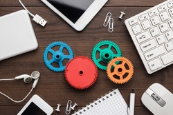 workflow and teamwork concepts with colorful gears different gadgets and office stationery on the wooden table