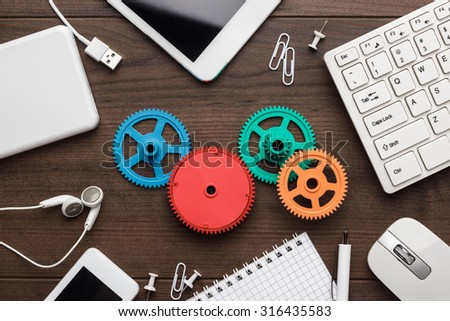 workflow and teamwork concepts with colorful gears different gadgets and office stationery on the wooden table #316435583