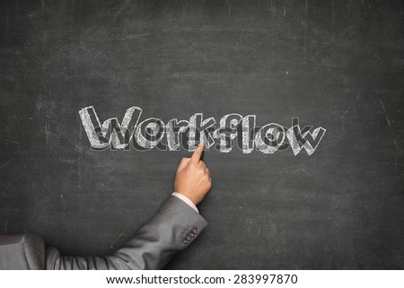 Workflow concept on black blackboard with businessman hand pointing