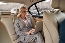 Working Anywhere. Attractive focused businesswoman in stylish classic wear working on laptop while sitting in the car. Business concept. Work concept. Success