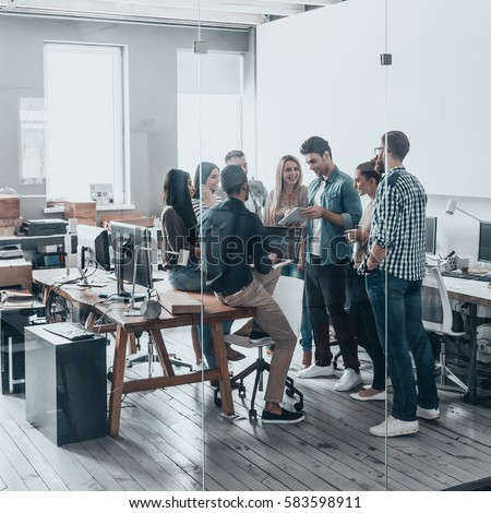 Working as one team. Full length of young modern people in smart casual wear having a meeting while standing behind the glass wall in the creative office