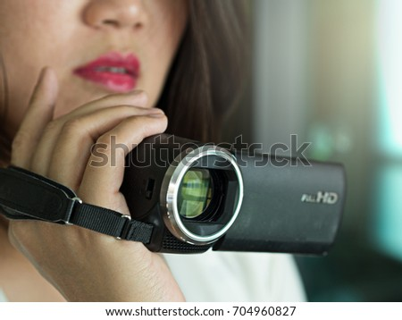Working Asian woman recording or taking a media video using video recorder, camcorder or video camera, close up face and hand