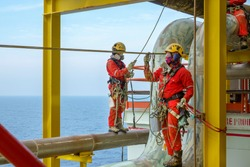 Working at height. A group of abseilers wearing red coverall and Personal Protective Equipment (PPE) standing on the piepeline managing their rope access with background open sea.