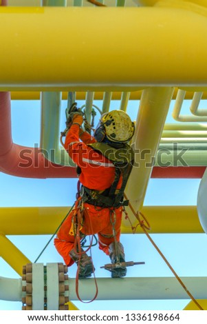 Working at height. An abseiler from rear view with dirty coverall wearing Personal Protective Equipment (PPE) hanging at life lines to remove dents at pippeline using air grinding machine.