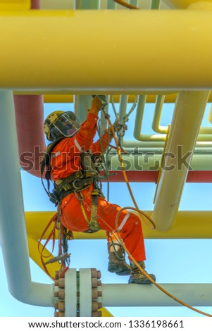 Working at height. An abseiler from side view with dirty coverall wearing Personal Protective Equipment (PPE) hanging at life lines to remove dents at pippeline using air grinding machine.