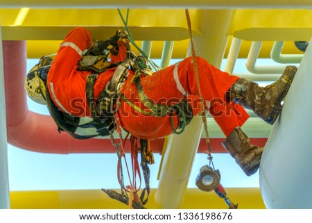 Working at height. An abseiler from side view with dirty coverall wearing Personal Protective Equipment (PPE) hanging at life lines to remove dents at pippeline using abseiling technique.