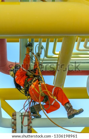 Working at height. An abseiler from side view with dirty coverall wearing Personal Protective Equipment (PPE) hanging at life lines to remove dents at pipeline using air grinding machine.