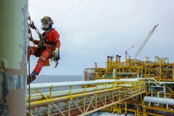 Working at height. An abseiler wearing Personal Protective Equipment (PPE) and fall protection device hanging at pipeline for painting activities with background oil and gas platform.