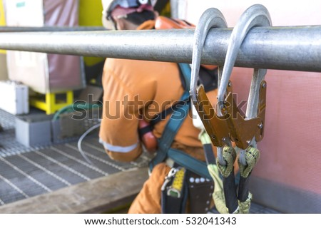 Working at height equipment. Fall arrestor device for worker with double hooks for safety body harness on selective focus. Worker as a background.
