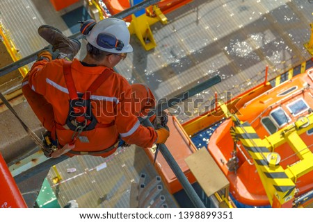 Working at height. Scaffold erector with fall arrestor device sitting on scaffold frames during working at height.