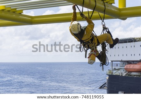Working at height. Working overboard. A commercial abseiler with fall arrestor device hanging on bridge pipeline structure at oil and gas platform. #748119055