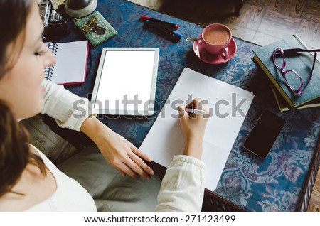 Working at home concept. Entrepreneur business woman writing and taking notes using her digital tablet on retro desk full of objects.