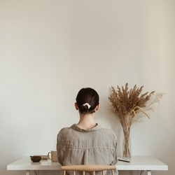 Working at home concept. Girl working at home. Modern home living room interior design. Girl boss, lady boss. Aesthetic minimalist workspace background. Blog, social media, web, magazine template.