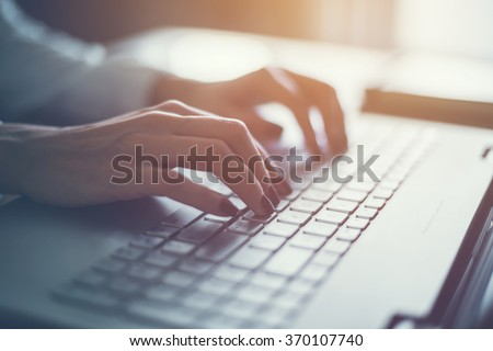 Working at home with laptop woman writing a blog. Female hands on the keyboard #370107740