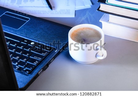 working at night, laptop with documents and cup of coffee on table