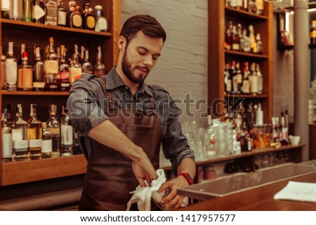 Working at the bar. Handsome attractive dark-haired bearded adult bartender wearing dark clothes and apron polishing glasses at the bar #1417957577