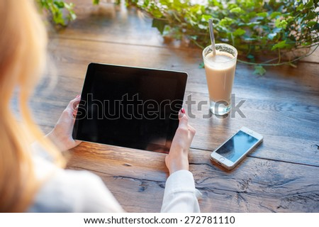Working at the cafe. Close up of female hands holding tablet computer on the wooden table with glass of latte and smartphone on it.