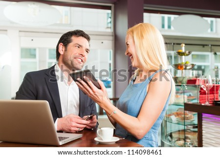 Working colleagues - a man and a woman - sitting in cafe working and drinking coffee