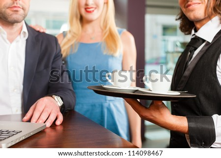 Working colleagues - a man and a woman - sitting in cafe working, the waiter serves coffee