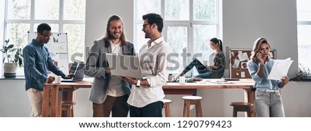 Working day in office. Group of young modern people in smart casual wear smiling and discussing something while working in the creative office #1290799423