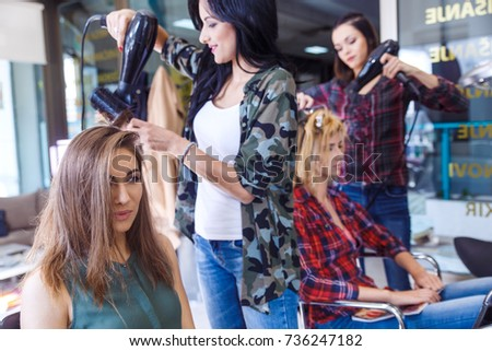 Working day inside the hair salon, hairdressers making hairstyle on two young woman. #736247182