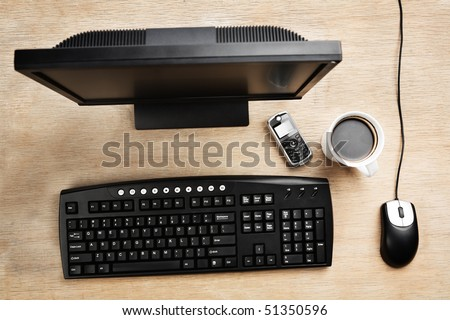 Working desk filled with Computer, cell phone and mug of coffee