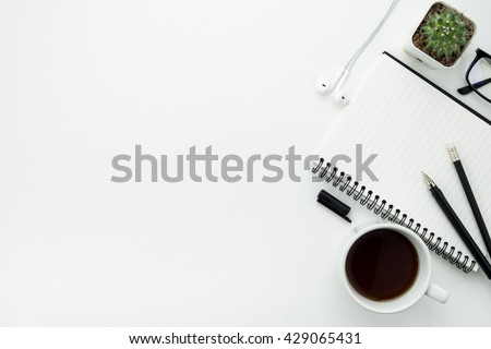 Working desk table with notebook, pen, pencil and cup of coffee. Top view with copy space.
