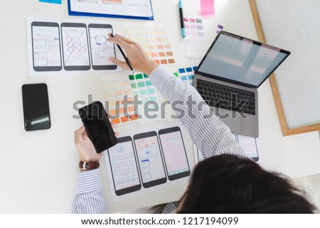 Working desk with hands sketching of screens for mobile responsive website development with UI/UX. Developing wireframe sketch layout design mockup on smartphone screen. #1217194099
