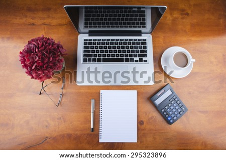 Working desk with spectacle, notebook, calculator, a cup of coffee, a flower jar and laptop