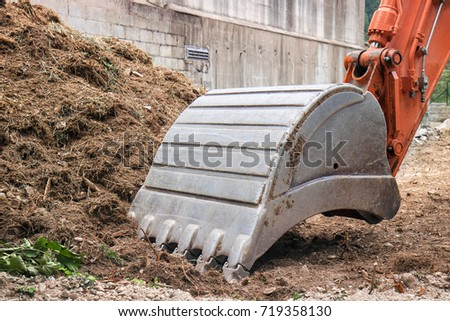 working digger in a construction site, closeup of heavy equipment #719358130
