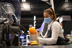 Working during corona virus pandemic. Cashier in grocery store wearing mask and gloves fully protected against the virus.